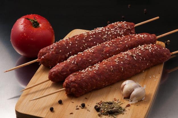 Lekkere rauwe lula-kebab met kruiden op een houten bord