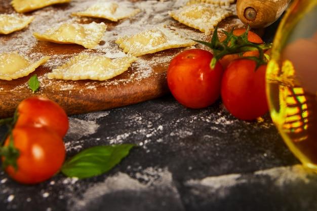 Lekkere rauwe ravioli met bloem, kerstomaatjes, zonnebloemolie en basilicum op een donkere ondergrond