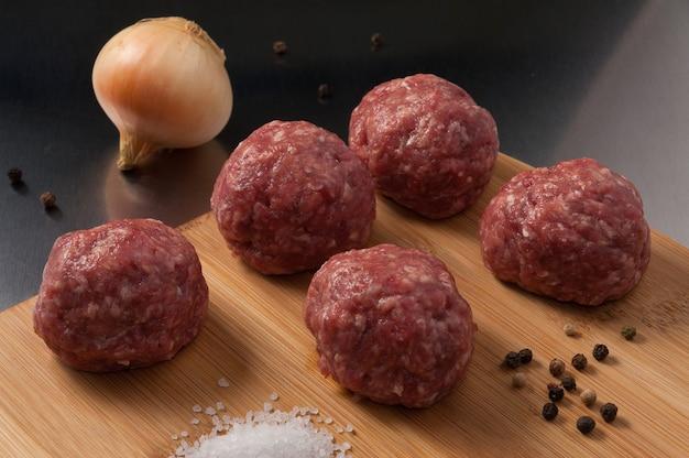 Lekkere rauwe rundvlees gehaktballetjes op een houten bord