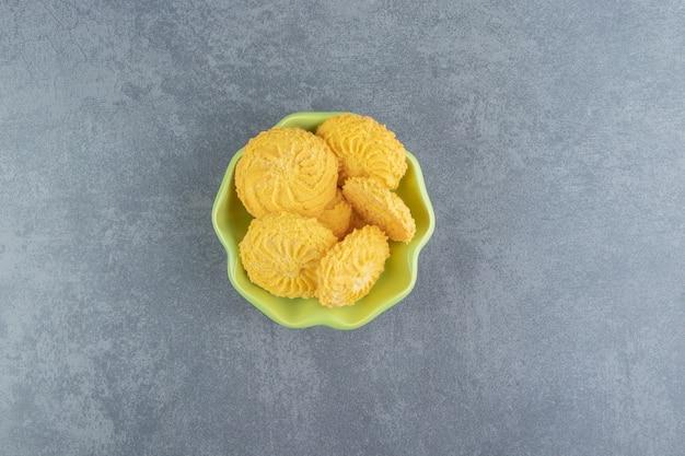 Lekkere ronde koekjes in groene kom.