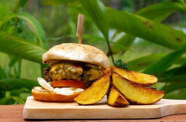 Lekkere runderburger met sla en ui geserveerd met frietjes op een houten tafel