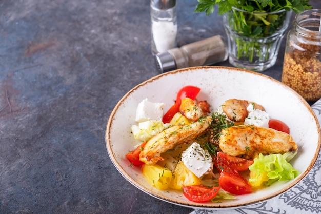 Lekkere salade met gebakken kip, tomaten, ananas, kaas en sla
