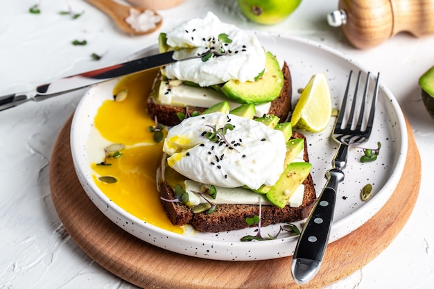 Lekkere sandwich met avocado en gepocheerd ei op houten snijplank, gezond heerlijk ontbijt of lunch