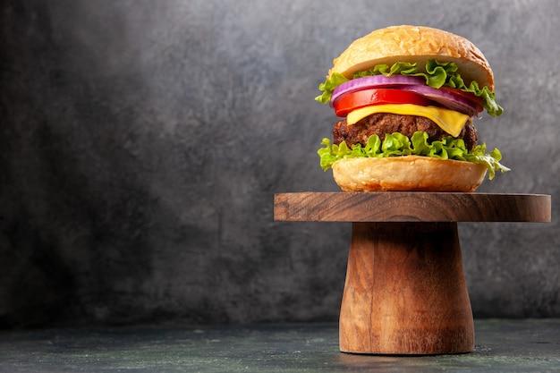 Lekkere sandwich op een houten bord aan de linkerkant op een donker gemengd kleuroppervlak met vrije ruimte