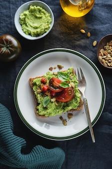 Lekkere sandwich op volkorenbrood met gepureerde avocado en tomaten
