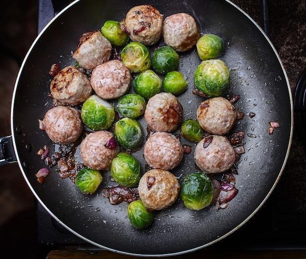 Lekkere sappige gehaktballetjes met spruitjes en gebakken ui gekookt in de pan
