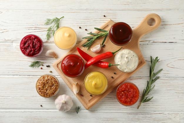 Lekkere sauzen in kommen, kruiden en bord op houten achtergrond, bovenaanzicht