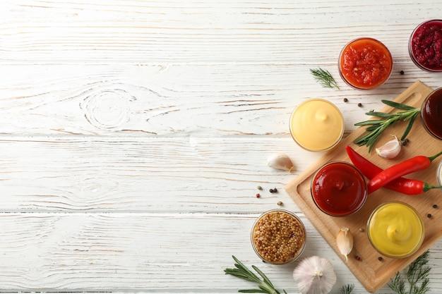 Lekkere sauzen in kommen, kruiden en karton op houten, bovenaanzicht
