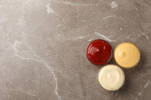 Lekkere sauzen in kommen op grijze achtergrond, ruimte voor tekst