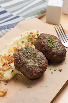 Lekkere schnitzels met aardappelpuree en gebakken uien close-up