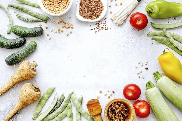 Lekkere smakelijke biologische boerderijgroenten met gezonde kruidenier op lichte achtergrond. gezond eten concept. bovenaanzicht