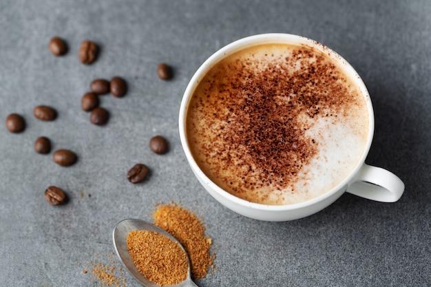 Lekkere smakelijke cappuccino in beker met bonen op betonnen tafel.
