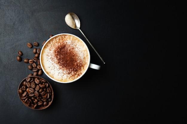 Lekkere smakelijke cappuccino in beker met bonen op donkere tafel.