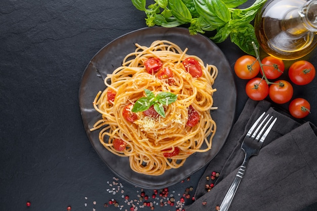 Lekkere smakelijke klassieke italiaanse spaghetti pasta met tomatensaus, kaas parmezaanse kaas en basilicum op plaat en ingrediënten voor het koken van pasta op donkere tafel. plat lag bovenaanzicht kopie ruimte.