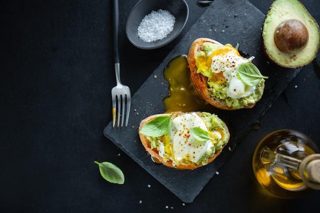Lekkere smakelijke toast met avocado en ei geserveerd op donker bord.