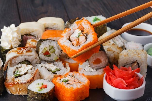 Lekkere smakelijke veelkleurige sushi broodjes set, geserveerd met sojasaus en eetstokjes