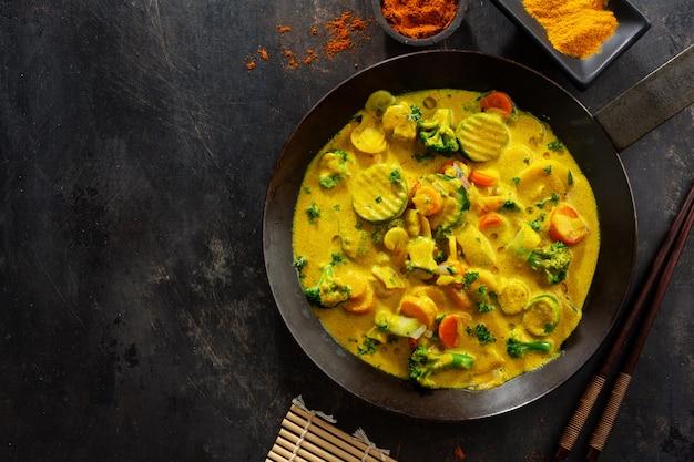 Lekkere smakelijke veganistische curry met groenten op pan. detailopname.