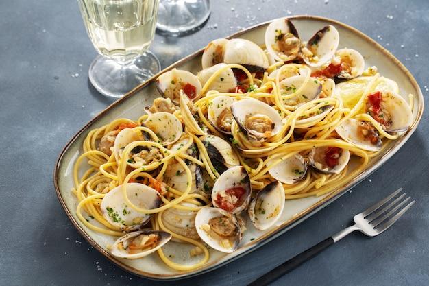 Lekkere smakelijke verse zelfgemaakte mosselen alle vongole zeevruchten pasta met knoflook en witte wijn op plaat. detailopname.