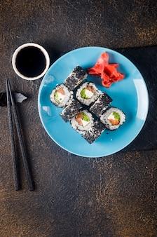 Lekkere sushibroodjes in zwarte sesam op blauw bord met zwarte eetstokjes, gember en wasabi op donkere achtergrond. sushimenu. bezorgservice japans eten.