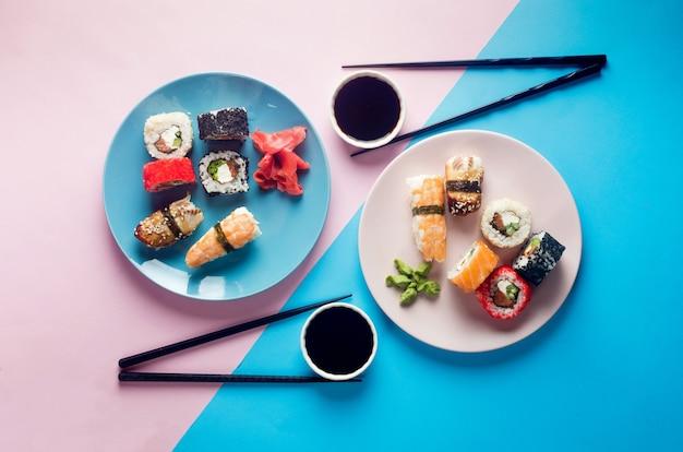 Lekkere sushibroodjes op blauwe plaat met sauzen, eetstokjes, gember en wasabi op gekleurde achtergrond. sushimenu. bezorgservice japans eten. geassorteerde sushi, broodjes, gunkan, nigiri.
