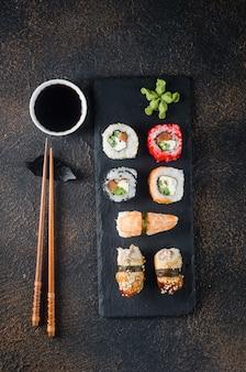 Lekkere sushibroodjes op zwarte plaat met sauzen, eetstokjes, gember en wasabi op donkere tafel. sushimenu. bezorgservice japans eten. geassorteerde sushi, broodjes, gunkans, nigiri.