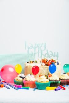 Lekkere taart met bessen en gelukkige verjaardagstitel in de buurt van set van muffins en ballonnen