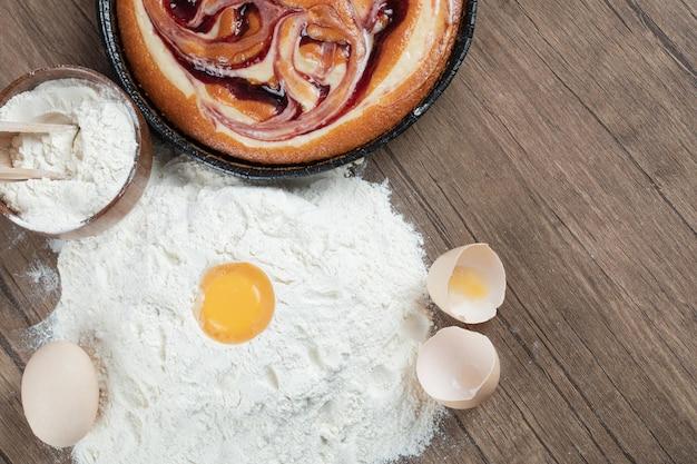 Lekkere taart met ingrediënten op houten tafel.