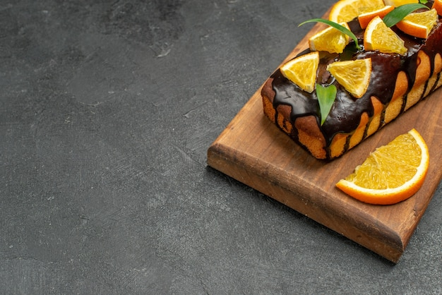 Lekkere taarten versierd met sinaasappels en chocolade op snijplank op zwarte tafel