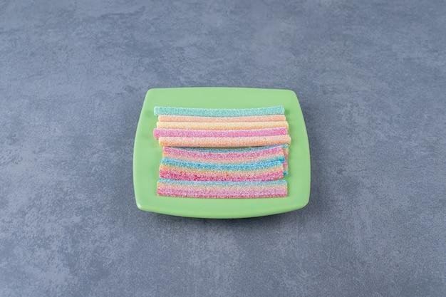 Lekkere touwvormige snoepjes op een bord op marmeren tafel.