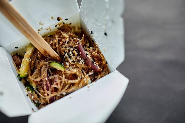 Lekkere udon-noedelspasta met tempuru, garnalenwok in doos en houten stokjes, japans gekruid eten