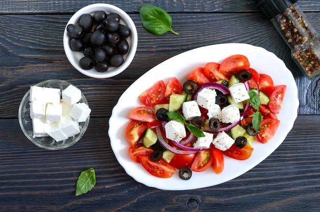 Lekkere vegetarische salade van tomaat, komkommer, rode ui en zwarte olijven