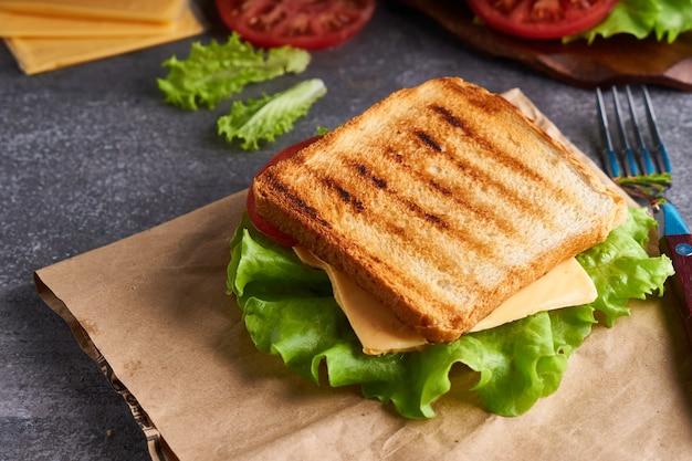Lekkere vegetarische sandwich met tomaten en kaas op een grijze stenen tafel exemplaarruimte