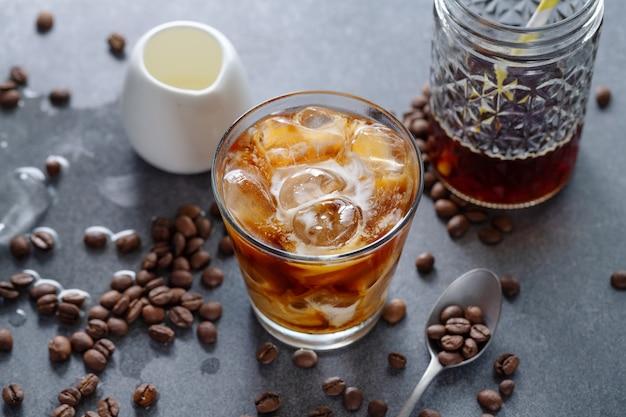 Lekkere verfrissende ijskoffie met ijsblokjes in glazen op lichte achtergrond. detailopname