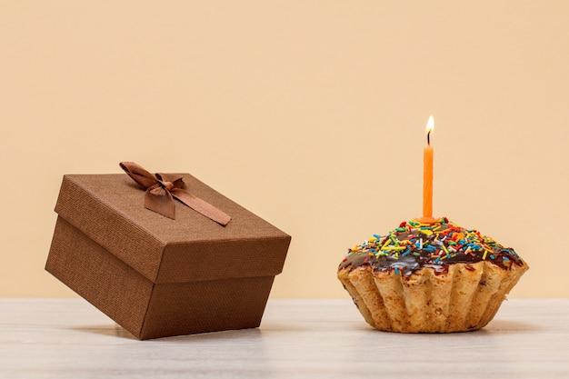 Lekkere verjaardagsmuffin met chocoladeglazuur en karamel, versierd met brandende feestelijke kaars en geschenkdoos op beige kleur achtergrond. gelukkige verjaardag minimaal concept.