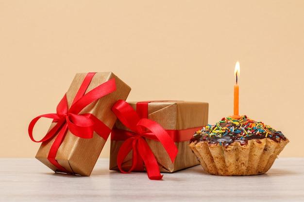 Lekkere verjaardagsmuffin met chocoladeglazuur en karamel, versierd met brandende feestelijke kaars en geschenkdozen op beige achtergrond. gelukkige verjaardag minimaal concept.