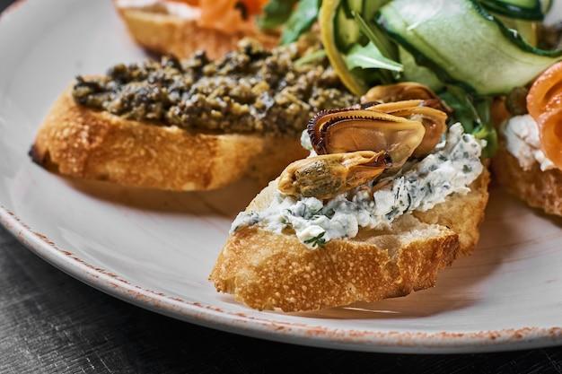 Lekkere verschillende italiaanse sandwiches met zeevruchten tegen rustieke houten achtergrond. crostini met kaas, rode vis, citroen en gesneden olijven, horizontale weergave met selectieve aandacht