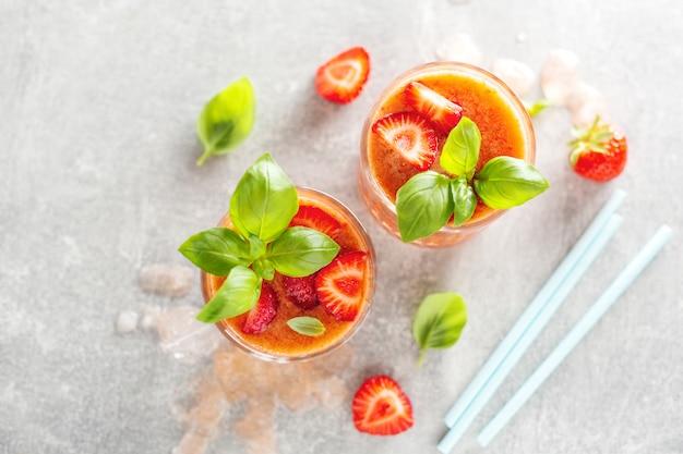 Lekkere verse drank met stawberry en basilicum geserveerd in glazen op betonnen tafel.