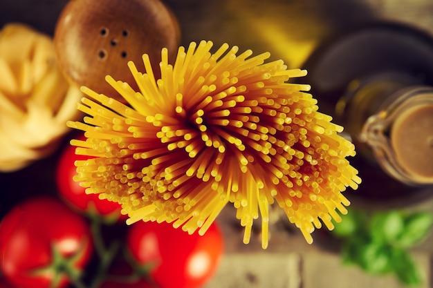 Lekkere verse kleurrijke italiaanse voedsel ruwe spaghetti op keukentafel op keukenachtergrond. koken of gezond voedselconcept.