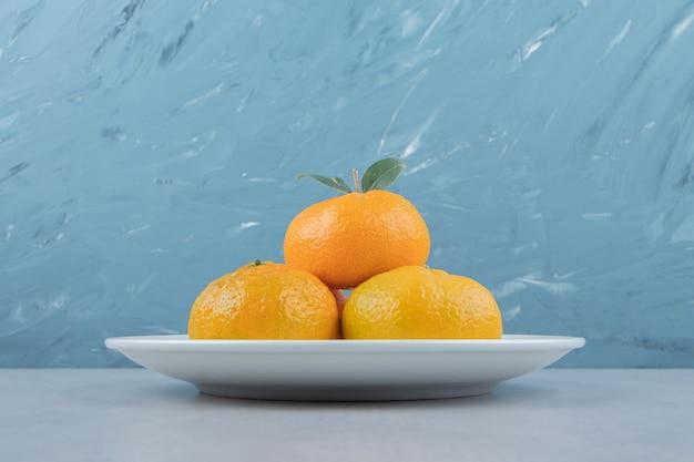 Lekkere verse mandarijnen op witte plaat.