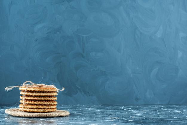 Lekkere wafels op een onderzetter, op de blauwe tafel.