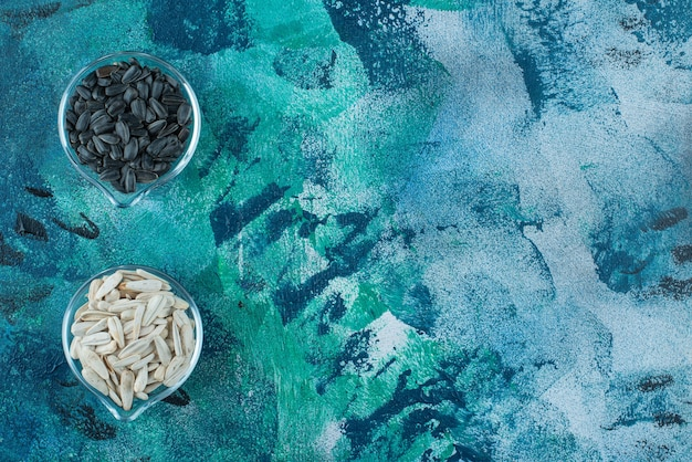 Lekkere witte en zwarte zonnebloempitten in een glazen kom, op de blauwe tafel.