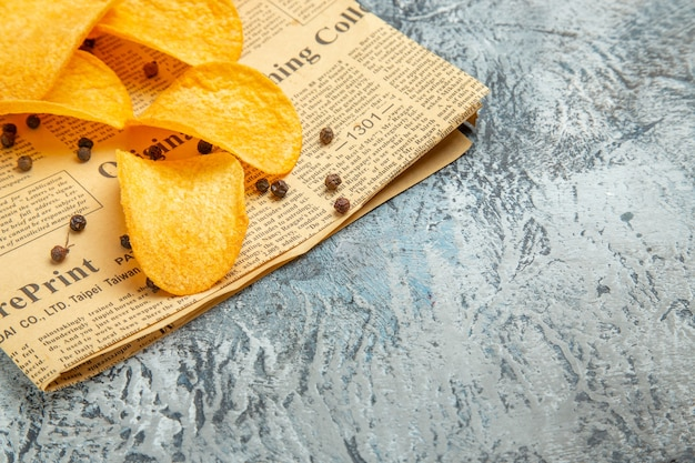 Lekkere zelfgemaakte chips en peperkom mayonaiseketchup op krant op grijze achtergrond