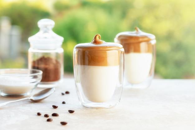 Lekkere zelfgemaakte dalgona koffie in glazen beker met ingrediënten, koffie en suger op een tafel op groene achtergrond. gecreëerd nieuw drankje tijdens quarantaine en zelfisolatie.