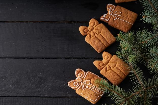 Lekkere zelfgemaakte koekjes met suikerglazuur op donkere tafel met spartak. kerst- en winterconcept close-up