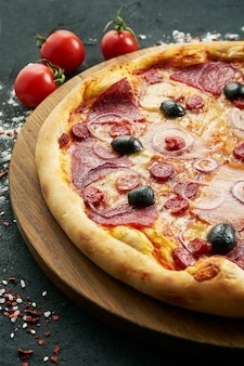 Lekkere, zelfgemaakte pizza met salami en warme worst, kaas en olijven op een houten bord op een zwarte tafel. traditionele italiaanse keuken. eten tafel