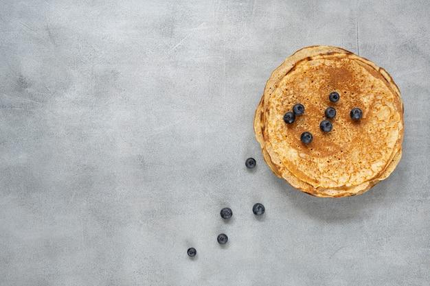 Lekkere zelfgemaakte rustieke pannenkoek op betonnen ondergrond. tafel bovenaanzicht. maslenitsa eten.