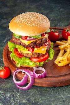 Lekkere zelfgemaakte sandwich tomaten peper op houten snijplank uien tomaat met stam frietjes op donkere kleur oppervlak