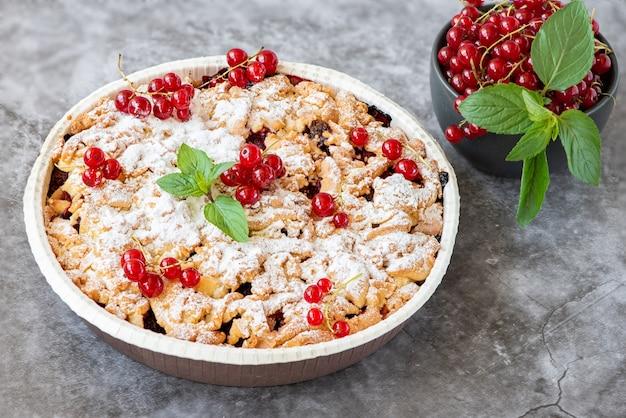 Lekkere zelfgemaakte taart en verse rode aalbessen in donkere kom op grijs.