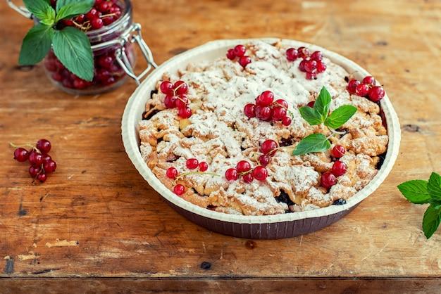 Lekkere zelfgemaakte taart en verse rode aalbessen in pot op oude houten tafel