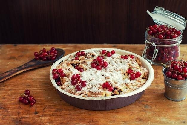 Lekkere zelfgemaakte taart en verse rode aalbessen in pot op oude houten tafel.